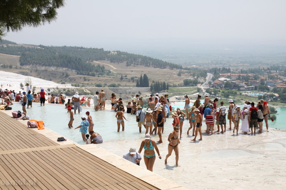 Turyści tłumnie okupują górny poziom wapiennych tarasów Pamukkale. Kto ma dość słońca, ma możliwość schronienia w cieniu drzew