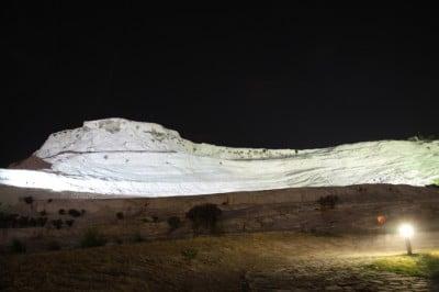 Nocą wapienne wzgórze w Pamukkale jest podświetlane. Warto przejść się do miejskiego parku, z którego widok na wapienne tarasy jest najlepszy