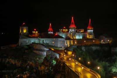 Czerwone kopuły z jakimiś czarnymi symbolami przypominającymi pająki. Oto zamek w Kamieńcu Podolskim widziany nocą.