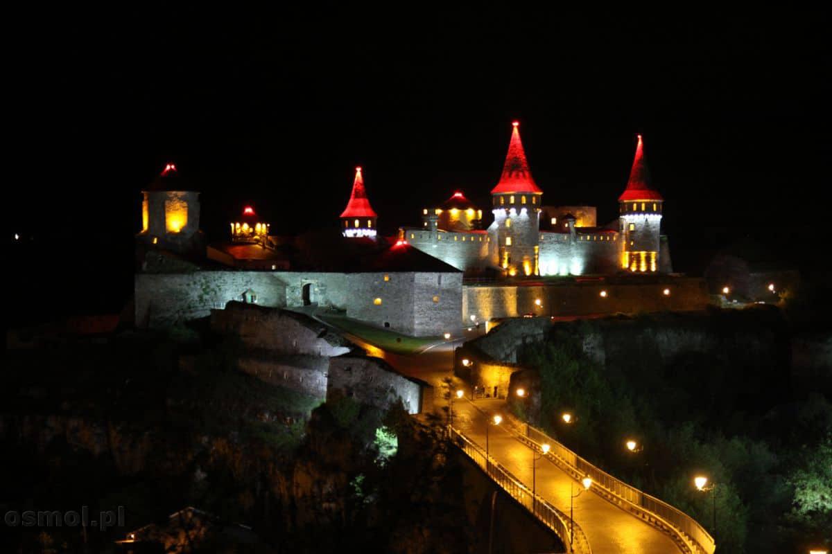 Czerwone kopuły z jakimiś czarnymi symbolami przypominającymi pająki. Oto zamek w Kamieńcu Podolskim widziany nocą