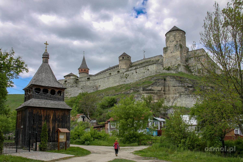 Zamek w Kamieńcu widziany z dołu. Tu też znajdziemy zwykłe domy, cerkiew oraz średniowieczne umocnienia broniące zamku