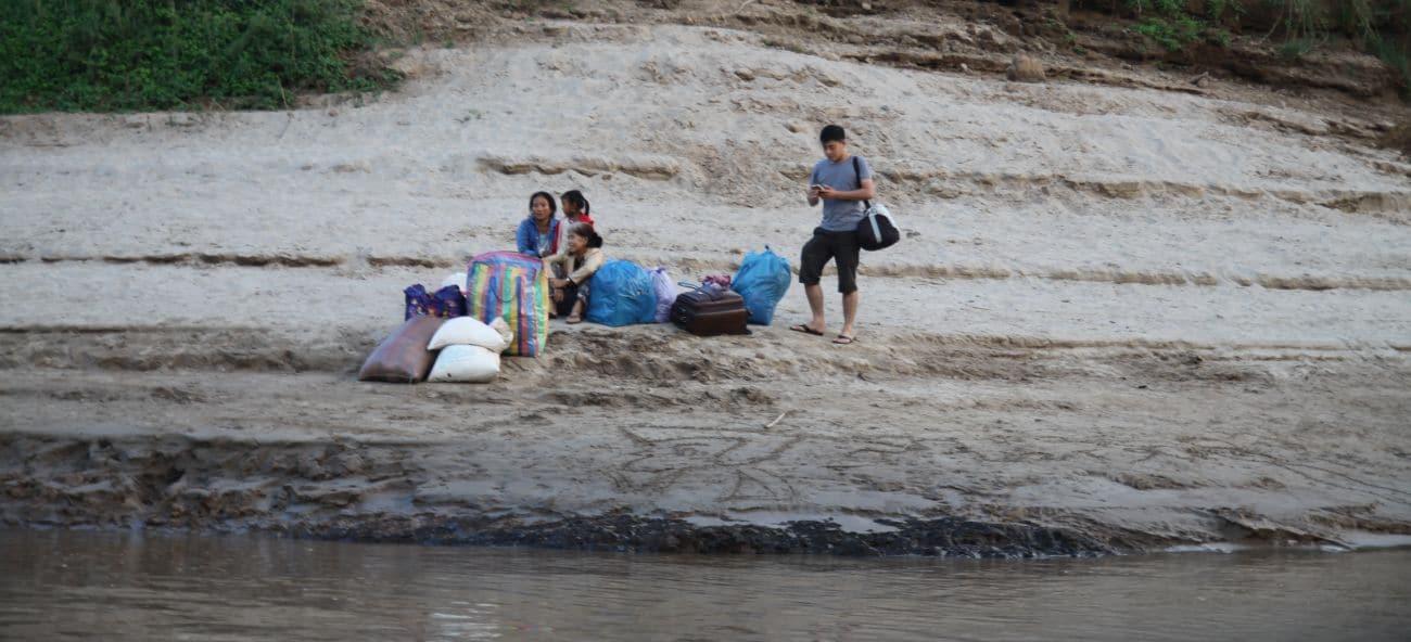 Laotańczycy na brzegu Mekongu oczekują na łódź, która zabierze ich w dół lub w górę rzeki. Bo Mekong to główny szlak komunikacyjny Laosu. I nawet turystyczne łodzie są jak taksówki.