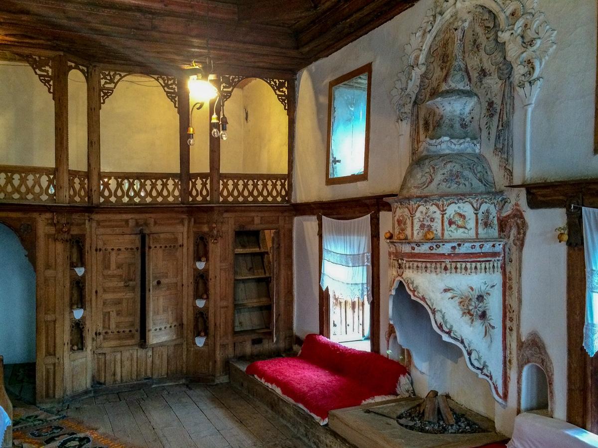 Sala reprezentacyjna w domu Skenduli w Gjirokastrze zachwyca zdobieniami w drewnie oraz pięknym kominkiem z owocowymi ornamentami