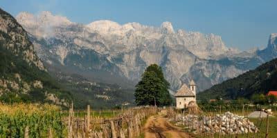 Widok na Theth w Albanii o poranku. Mimo, że to najbardziej znana i turystyczna miejscowość w Albanii, wcale nie przypomina znanych nam górskich kurortów. Ale za to ma specyficzny klimat miejsca odciętego od świata, bo też i zimą nie zawsze drogi prowadzące do Theth są przejezdne.