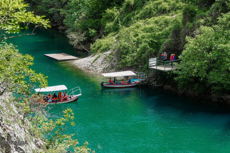 Łódki na rzece, czekające na turystów przed jaskinią Vrelo.