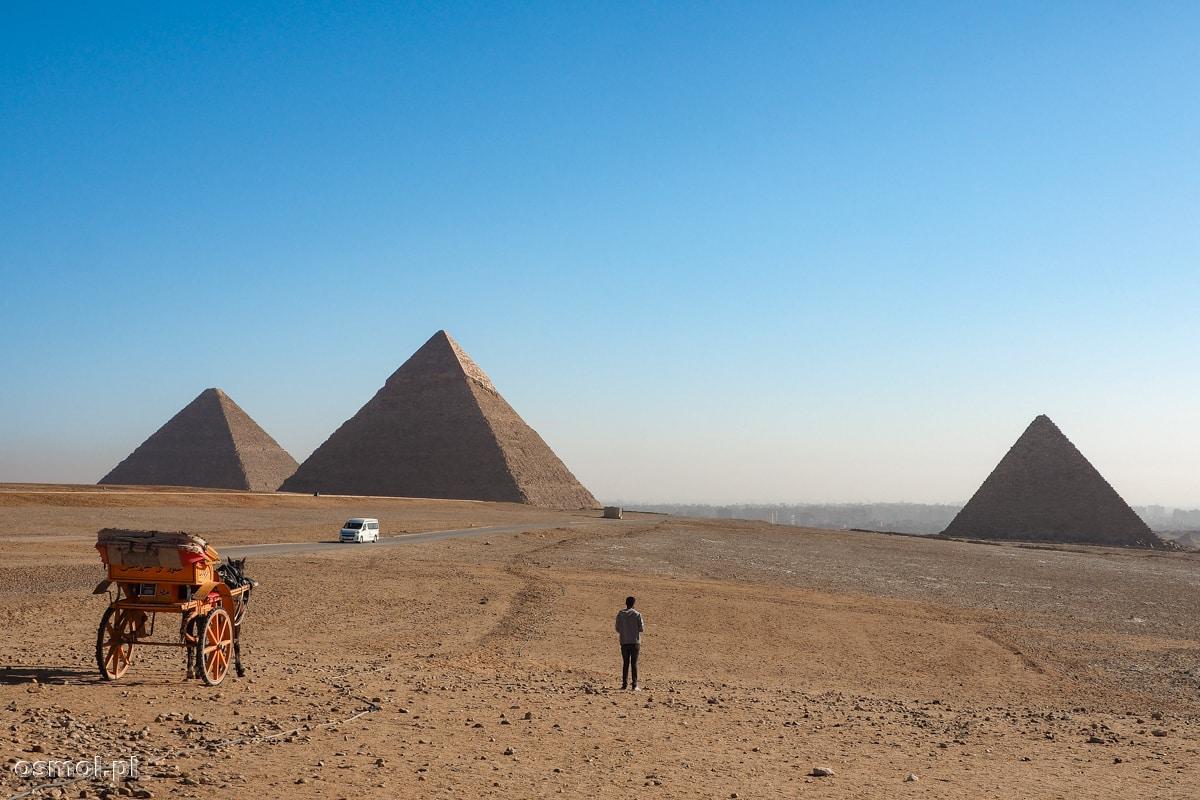 Bryczka i samochód na tle piramid w Gizie. A wszystko widziane z punktu widokowego, do którego można podejść lub dać się zawieźć - właśnie taką bryczką lub minivanem.