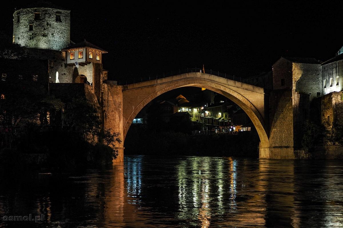 Podświetlony nocą most w Mostarze odbija się w płynącej pod nim Neretwie