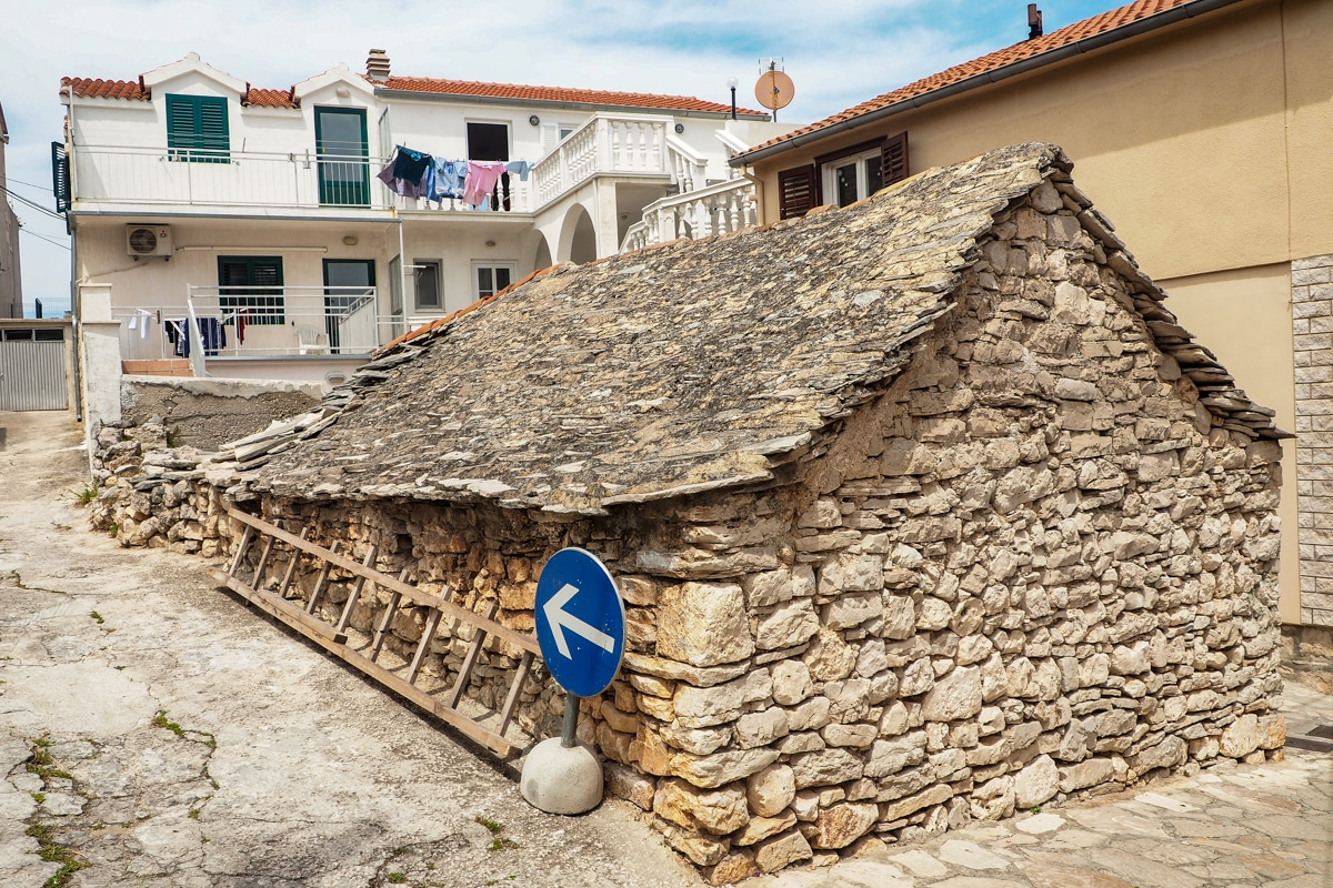 Stary budynek zbudowany w całości z kamienia i kryty kamiennym dachem