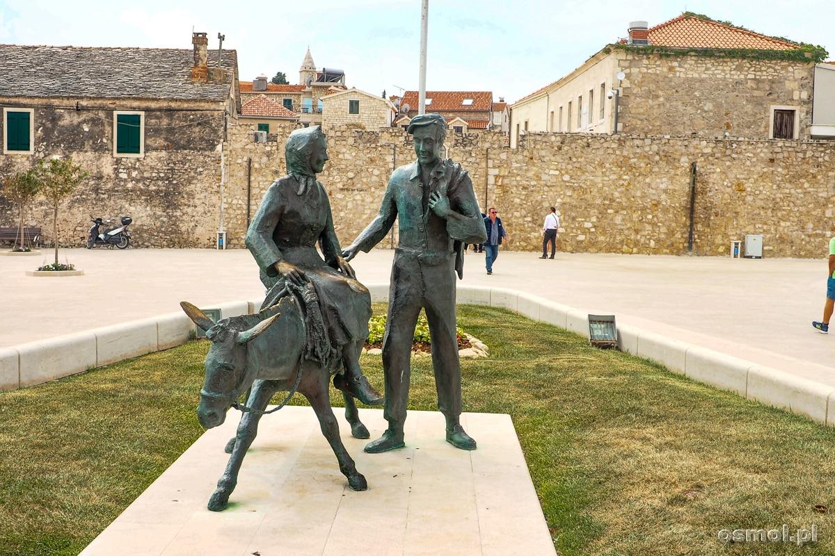 Pomnik pary z osiołkiem stojący przed wejściem do starej części Primosten