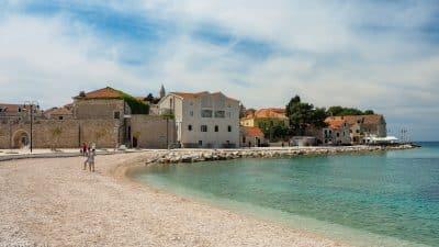 Primosten. Widok na plażę i dawne mury obronne miasta