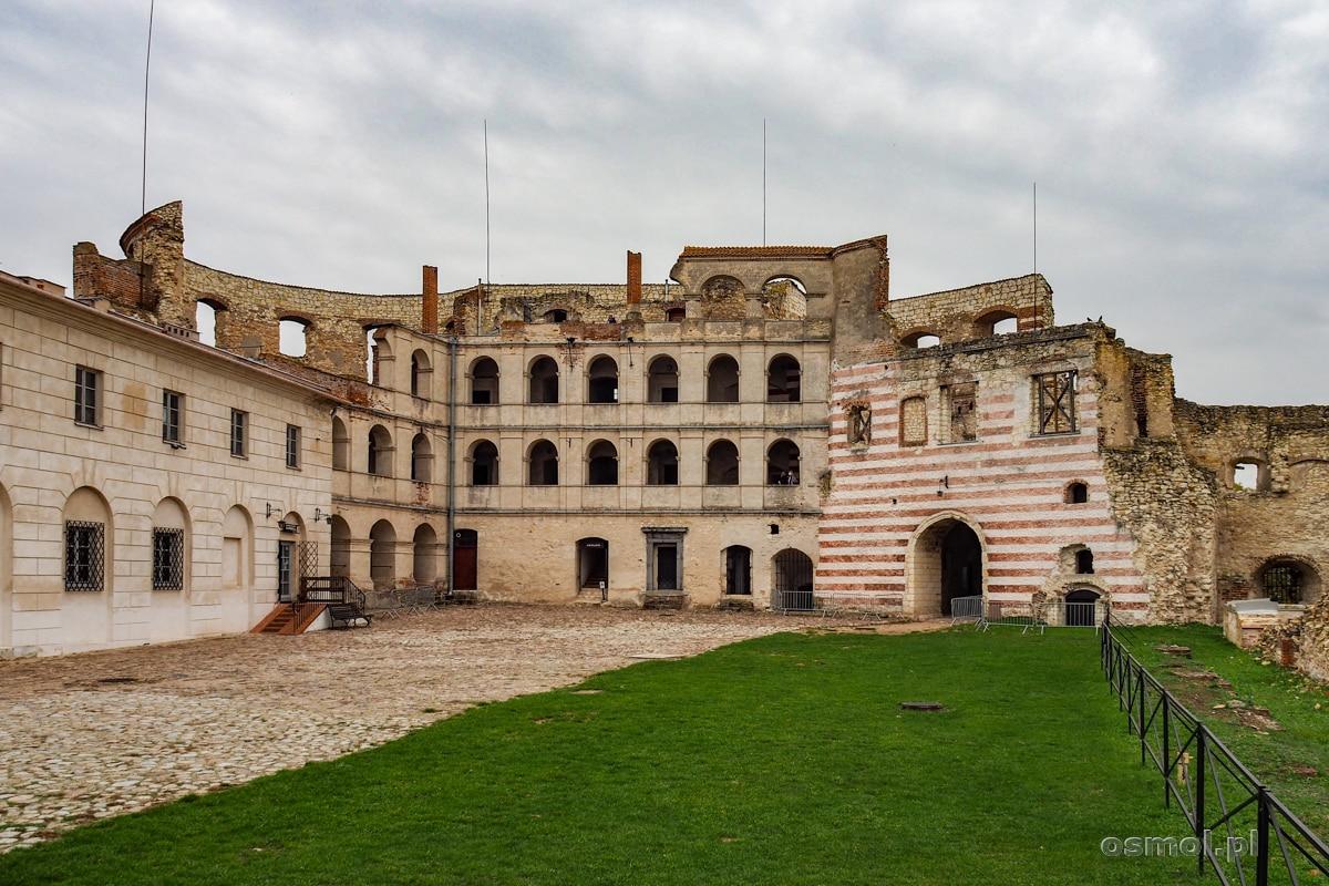 Dziedziniec zamku w Janowcu z arkadami i czerwonymi pasami na starym murze