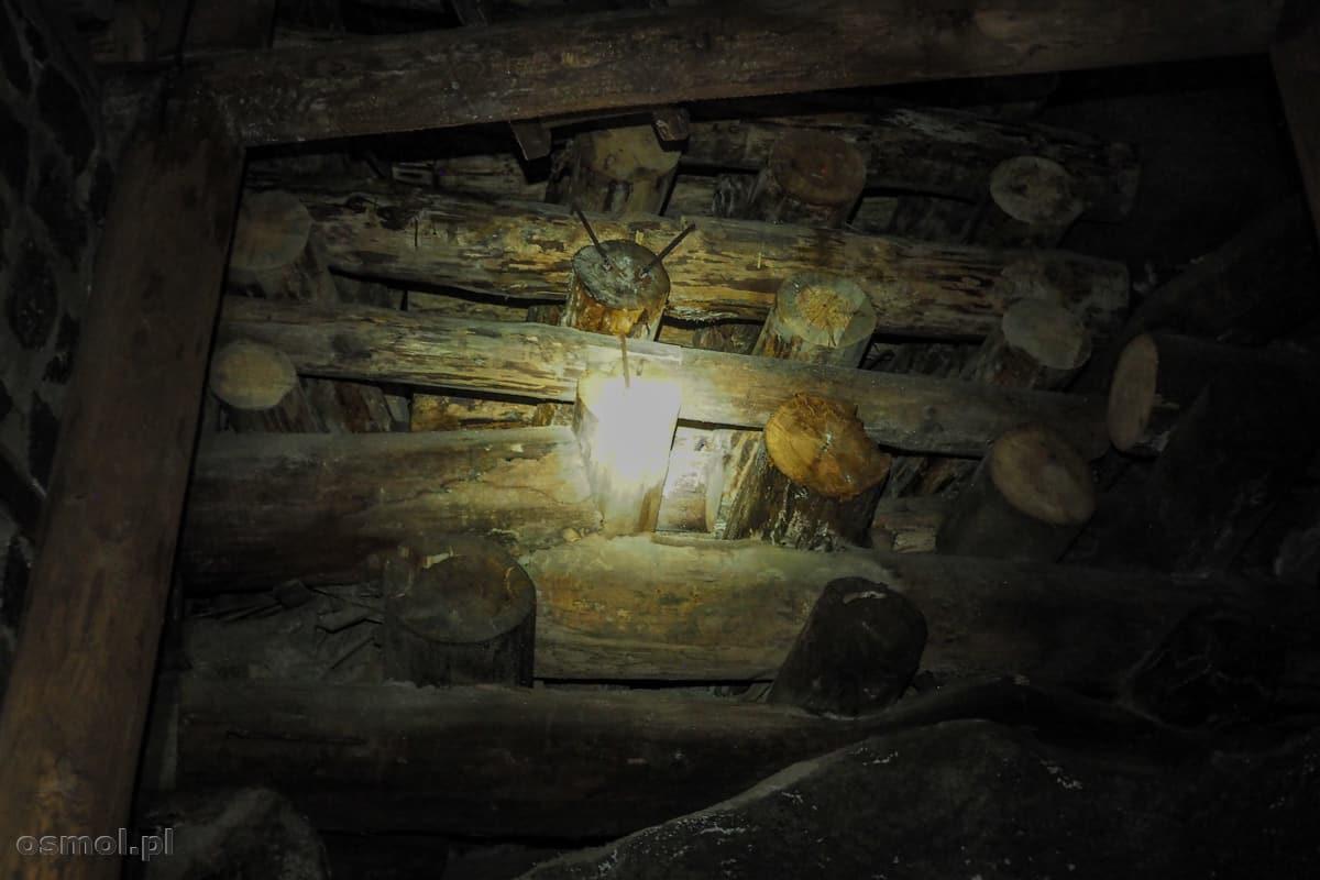 Promień górniczej lampy pełga po drewnianych kasztach podtrzymujących stropy i ściany